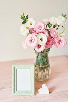 Fotolijst en bloemen in een vaas op tafel