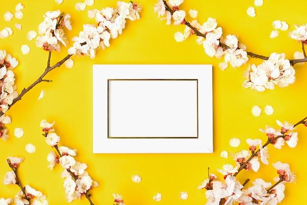 Fotolijst en takjes abrikozenboom met witte bloemen