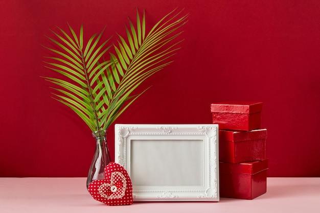 Fotolijst en valentijnsdag harten, palmblad en rode geschenkdozen op rode achtergrond. valentijnsdag concept.