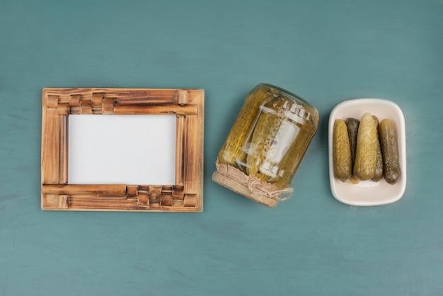 Fotolijst, ingelegde komkommers en verse komkommers op blauwe tafel.