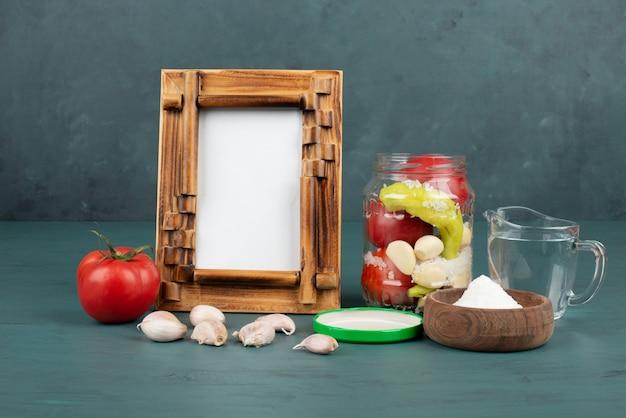 Fotolijst, ingemaakte groenten in glazen pot en zoute kom op blauwe ondergrond met verse tomaat en knoflook.
