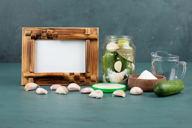 Fotolijst, ingemaakte groenten in glazen pot en zoutkom op blauwe ondergrond met verse komkommer en knoflook.