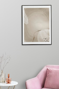 Fotolijst met abstracte kunst bij een roze fluwelen fauteuil