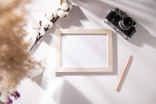 Fotolijst met katoen en camera op tafel
