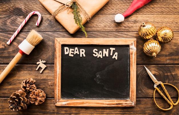 Fotolijst met lieve santa inscriptie in de buurt van huidige doos, haken en ogen en ornament ballen