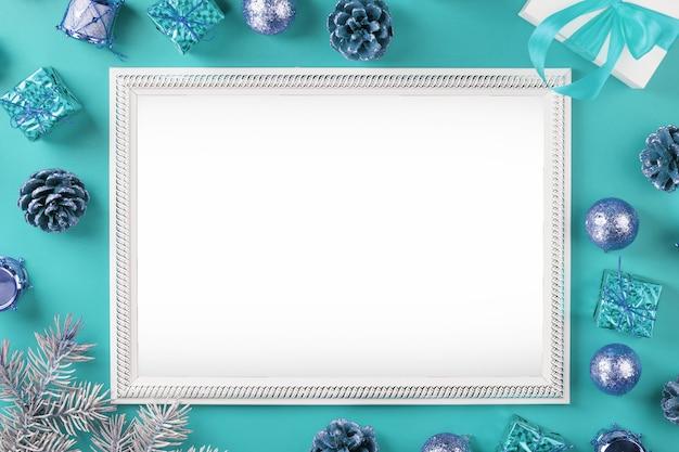 Fotolijst met vrije witte ruimte rond kerstboomversieringen en cadeaus op een blauwe achtergrond. bovenaanzicht, vrije ruimte voor tekst