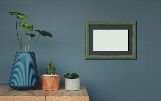 Fotolijst mockup hangend aan de grijze muur. omringd door groene plant in vaas en pot