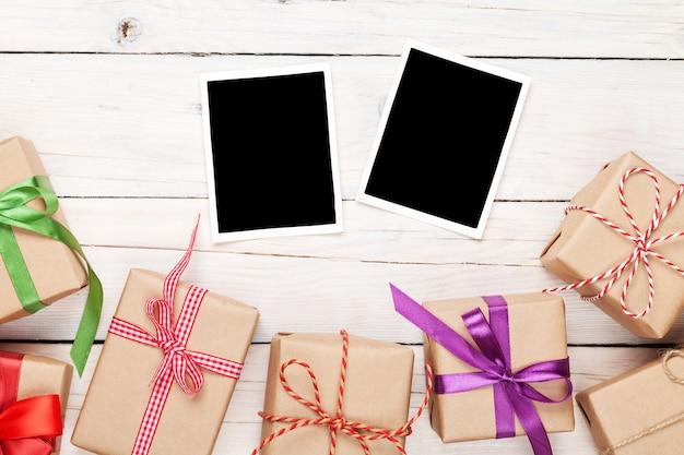 Fotolijsten en geschenkdozen met linten over witte houten tafel achtergrond
