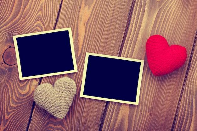 Fotolijsten en handgemaakte valentijnsdag speelgoed harten over houten achtergrond. getinte afbeelding