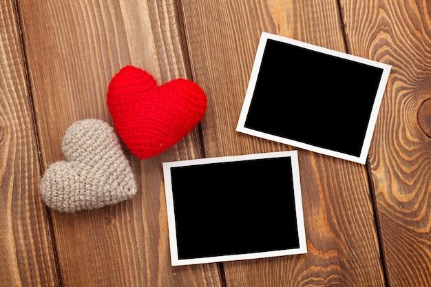 Fotolijsten en handgemaakte valentijnsdag speelgoedharten op houten achtergrond