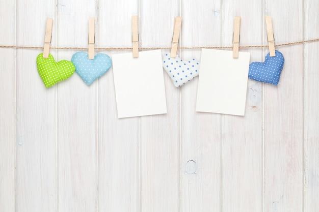 Fotolijsten en valentijnsspeelgoedharten over houten achtergrond