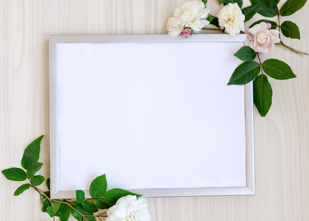 Fotolijstje versierd met groene bladeren en roze bloemen op beige pastel achtergrond. lege witte ruimte voor tekst. bespotten met kopieerruimte. plat leggen. wenskaart concept