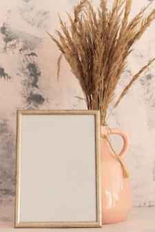 Fotolijstmodel en boeket gedroogde bloemen in een crème en roze vaas bij een roze muur