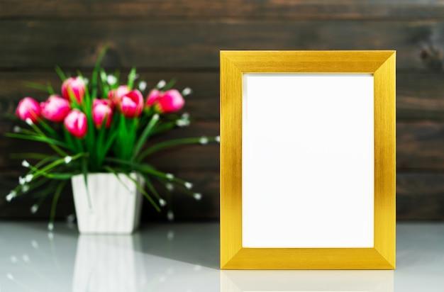 Fotomodel met gouden frame en kunstbloemenvaasboeket boven tafel met houten muurachtergrond