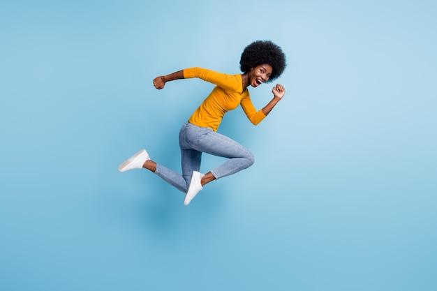 Fotoportret op volledige grootte van actief meisje dat in de lucht loopt geïsoleerd op pastelblauw gekleurde achtergrond