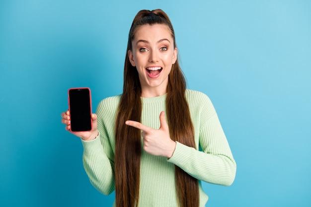 Fotoportret van brunette meisje wijzende vinger naar telefoon met lege ruimte open mond geïsoleerd op pastelblauw gekleurde achtergrond
