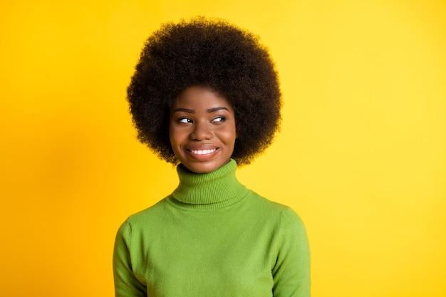 Fotoportret van een afro-amerikaans meisje dat naar de zijkant kijkt en denkt dromend geïsoleerd op een levendige geelgekleurde achtergrond