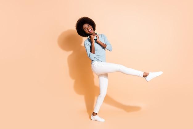 Fotoportret van een afro-amerikaans meisje met een groenblauwe koptelefoon om de nek die op een been staat geïsoleerd op een pastelbeige gekleurde achtergrond