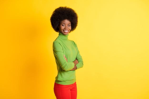 Fotoportret van een afro-amerikaanse freelancer die met gevouwen armen staat en lacht, geïsoleerd op een levendige geel gekleurde achtergrond