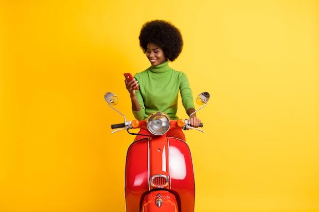 Fotoportret van een donkerbruine vrouw met een zwarte huid in vrijetijdskleding die een rode motor met een smartphone bestuurt, geïsoleerd op een levendige gele gekleurde achtergrond