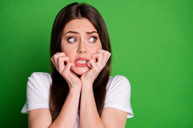 Fotoportret van een doodsbange vrouw die het gezicht aanraakt met twee handen die naar lege ruimte kijken geïsoleerd op een levendige groen gekleurde achtergrond