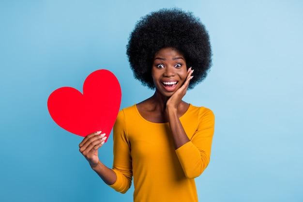 Fotoportret van een gelukkig lachend meisje met een zwarte huid dat een rode papieren hartkaart toont die de wang aanraakt, geïsoleerd op een helderblauwe kleurachtergrond