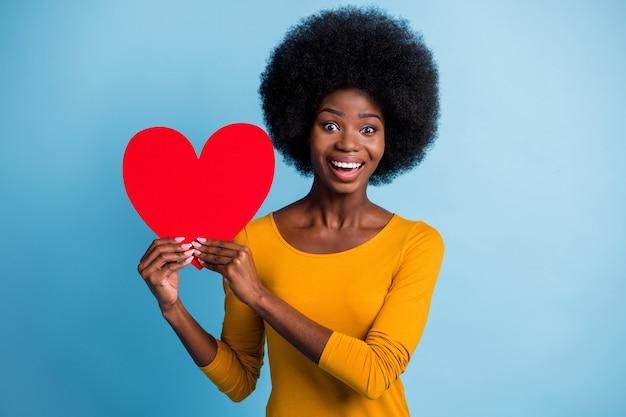 Fotoportret van een gelukkig lachende vrouw met een zwarte huid die een rood papieren symbool van een liefdeshart houdt dat op een helderblauwe achtergrond wordt geïsoleerd