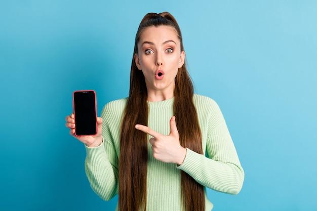 Fotoportret van een geschokt meisje dat met de vinger naar de telefoon wijst met een lege ruimte die een groene trui draagt, geïsoleerd op een pastelblauwe achtergrond