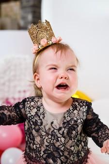 Fotoportret van een jarig meisje van 1 jaar oud in een roze jurk met roze ballonnen. het kind huilt op de vakantie, de emoties van kinderen. meisje huilt