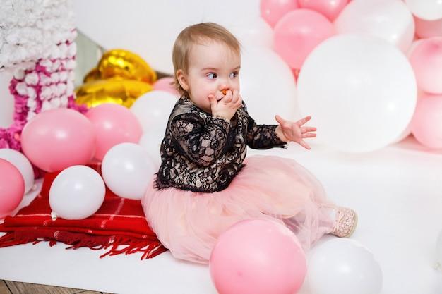 Fotoportret van een jarig meisje van 1 jaar oud in een roze jurk met roze ballonnen. het kind op de vakantie glimlacht, de emoties van kinderen. verjaardagsfeest