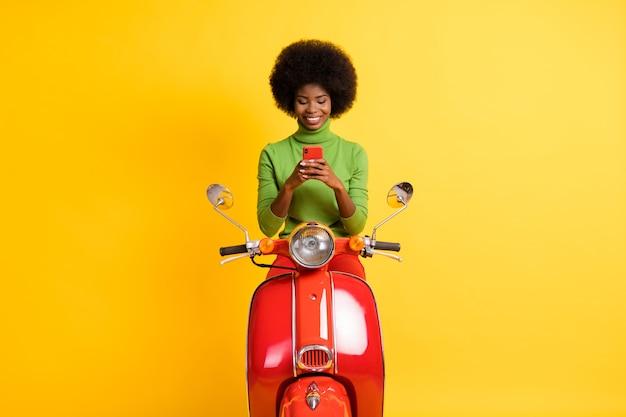 Fotoportret van een jonge brunette vrouw scooterrijder met rode smartphone in twee handen met vrijetijdskleding geïsoleerd op een levendige geel gekleurde achtergrond