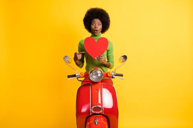 Fotoportret van een jonge, vrolijke, opgewonden afro-amerikaanse fietservrouw die met de vinger wijst naar een grote rode hartkaart die op een levendige geelgekleurde achtergrond wordt geïsoleerd