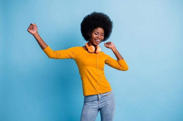 Fotoportret van een mooi zwart gevild meisje met een koptelefoon die danst in de disco, geïsoleerd op een levendige blauwe kleurachtergrond