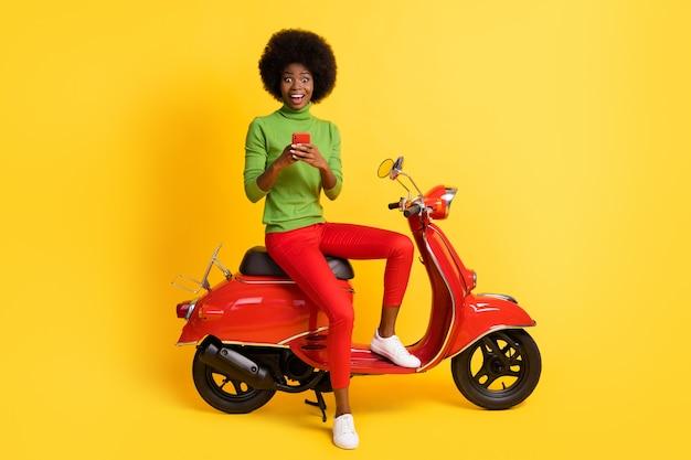 Fotoportret van een opgewonden, extatisch brunette meisje op een rode motorfiets met een mobiele telefoon in een casual outfit geïsoleerd op een felgele achtergrond