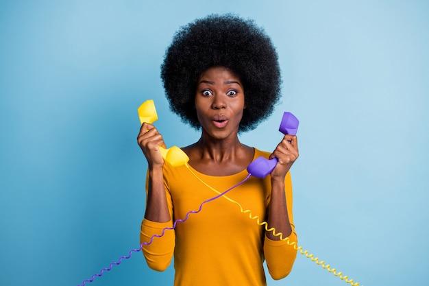 Fotoportret van een verbaasde, krullende vrouw met een zwarte huid die twee retro-telefoontoestellen vasthoudt met draden geïsoleerd op een levendige blauwe kleurachtergrond
