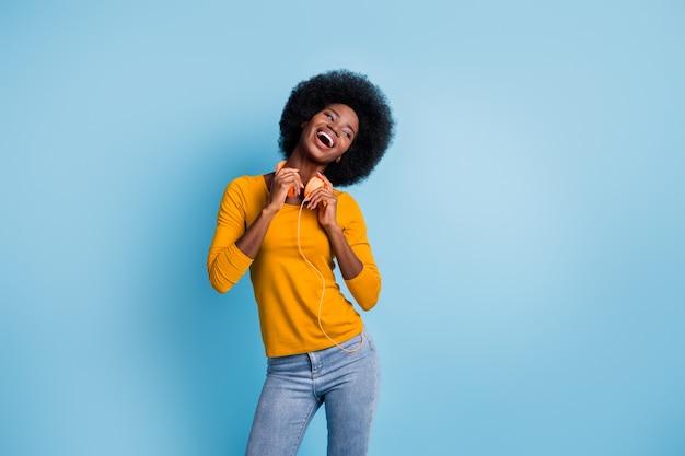 Fotoportret van een vrolijk lachend meisje met een zwarte huid dat een koptelefoon draagt die vrolijk lacht, geïsoleerd op een helderblauwe kleurachtergrond