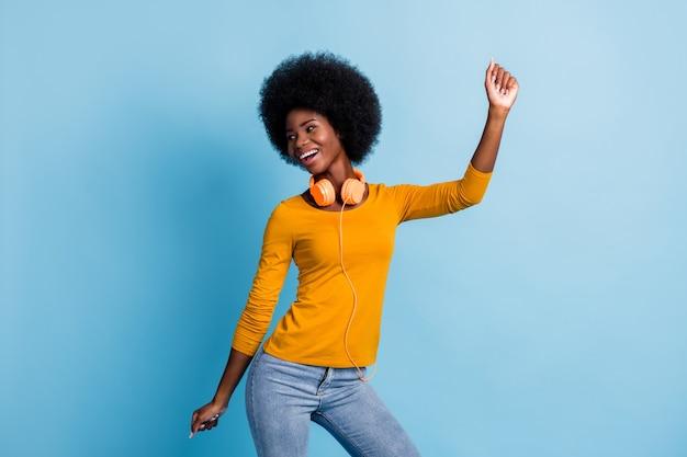 Fotoportret van een vrolijk lachend meisje met een zwarte huid met oortelefoons die dansen op een feestweekend geïsoleerd op een felblauwe kleurachtergrond