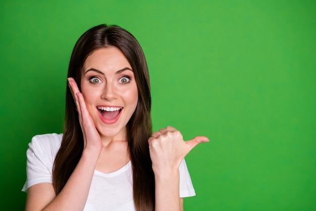 Fotoportret van een vrolijk meisje dat met de vinger wijst naar een lege ruimte die het gezicht aanraakt met één hand geïsoleerd op een levendige groen gekleurde achtergrond