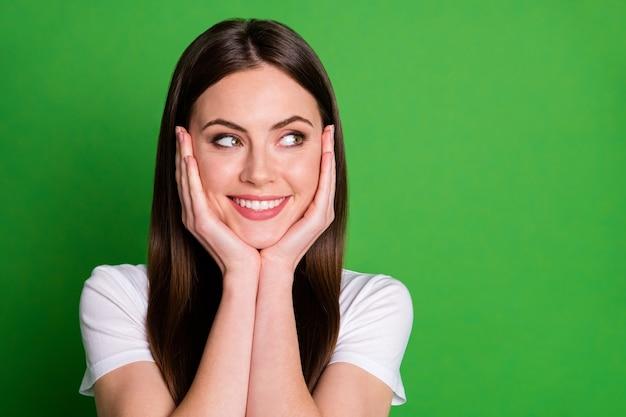 Fotoportret van een vrouw die de wangen van het gezicht aanraakt met twee handen die naar lege ruimte kijken geïsoleerd op een levendige groen gekleurde achtergrond