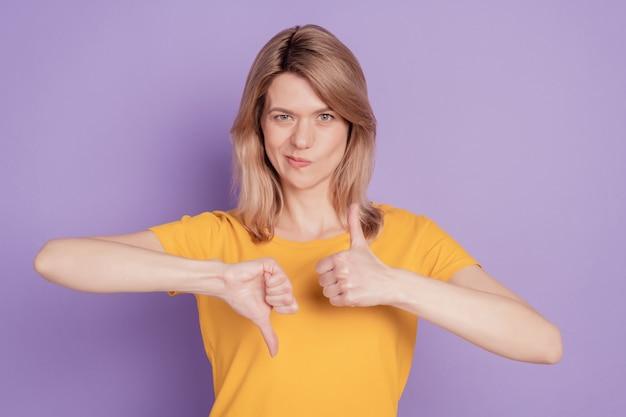 Fotoportret van een vrouw die duim omhoog toont en besluit besluit teken geïsoleerd op violet gekleurde achtergrond