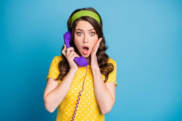 Fotoportret van een vrouw die het gezicht aanraakt met de hand open mond pratend over een paarse telefoon geïsoleerd op een pastel lichtblauw gekleurde achtergrond
