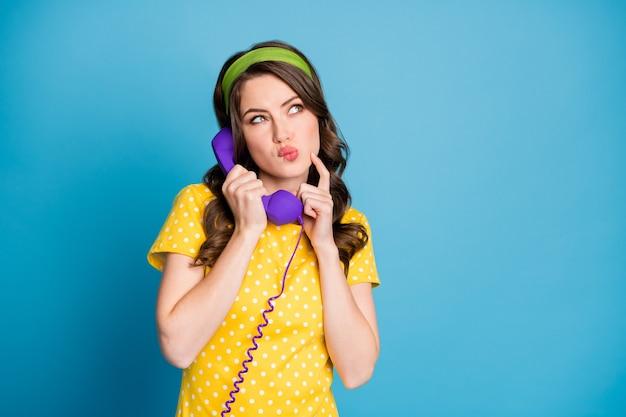 Fotoportret van een vrouw die het gezicht aanraakt met een vinger die een paarse telefoon vasthoudt die op een pastelkleurige lichtblauwe achtergrond wordt geïsoleerd