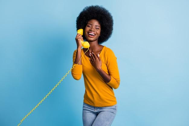 Fotoportret van een vrouw met een zwarte huid die praat op een retrotelefoon die de handset houdt met een draad die lacht geïsoleerd op een felblauwe kleurachtergrond