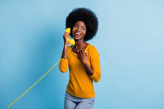Fotoportret van een vrouw met een zwarte huid die praat op een retrotelefoon die een gele handset houdt met draad geïsoleerd op een levendige blauwe kleurachtergrond