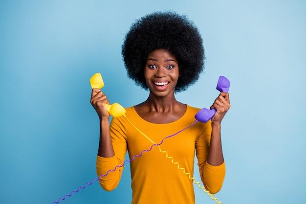 Fotoportret van een vrouw met een zwarte huid die twee retro-telefoontoestellen vasthoudt met draden geïsoleerd op een levendige blauwe kleurachtergrond