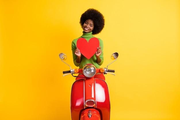 Fotoportret van een zwart gevild meisje op een motorfiets met een grote rode hartbriefkaart in twee handen geïsoleerd op een levendige gele gekleurde achtergrond