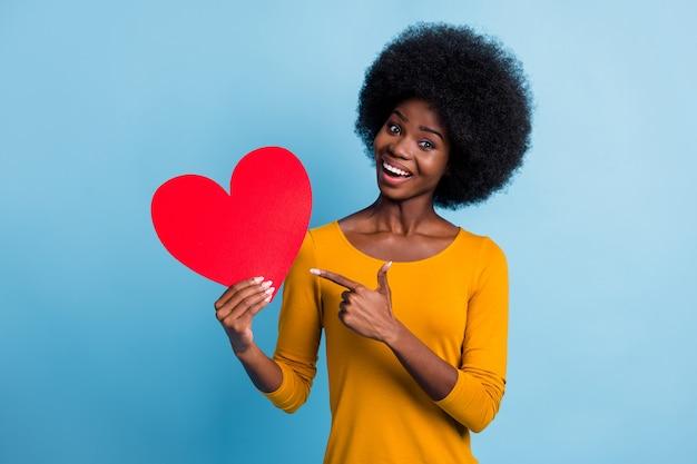 Fotoportret van gelukkig lachend meisje met zwarte huid wijzend op symbool van valentijnsdag hartkaart geïsoleerd op helderblauwe kleur achtergrond