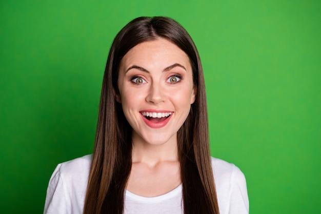 Fotoportret van gelukkig opgewonden meisje geïsoleerd op levendige groen gekleurde achtergrond