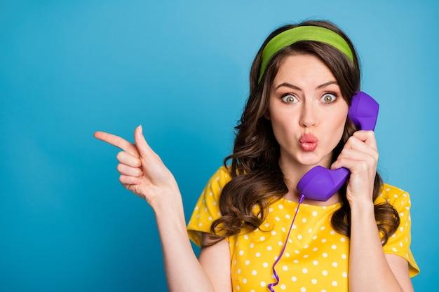 Fotoportret van geschokt meisje met dikke lippen wijzende vinger naar lege ruimte met paarse telefoon geïsoleerd op pastel lichtblauw gekleurde achtergrond