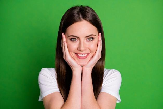 Fotoportret van glimlachend meisje wat betreft gezichtswangen met twee handen geïsoleerd op levendige groen gekleurde achtergrond